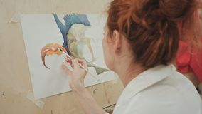Künstlerin, die ein Bild im Studio bei der Unterhaltung am Telefon malt Lizenzfreie Stockfotografie