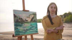 Künstlerin und ihre Landschaftsmalerei im hellen Sonnenschein im Freien stock video