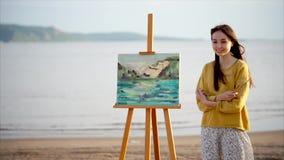 Künstlerin und ihre Landschaftsmalerei im hellen Sonnenschein im Freien stock video footage