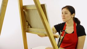 Künstlerinmalerei mit Malerpinsel Die Frau zeichnet ein Bild Der Künstler auf einem weißen Hintergrund zeichnet auf ein Gestellöl stock video