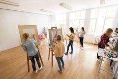 Künstlerinnen mit den Bürsten, die an der Kunstakademie malen Stockfotografie