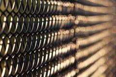 Künstlerische Ansicht des schwarzen Kettengliedzauns im Abendsonnenlicht stockfoto