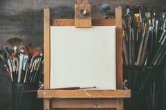 Künstlerische Ausrüstung in einem Künstlerstudio: leeres Künstlersegeltuch und -bürsten Lizenzfreie Stockfotos