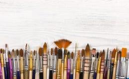 Künstlerische Bürsten auf hellem hölzernem Hintergrund Stockbild
