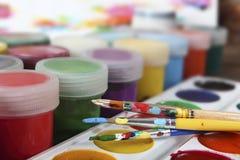 Künstlerische Bürsten und helle Aquarell- und Acrylfarben auf dem Künstler ` s Schreibtisch Nahaufnahme Fokus auf den Händen Stockbilder