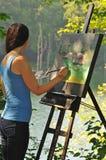 Künstlerische Frau acrylsauer draußen malend auf Segeltuch Lizenzfreie Stockfotos