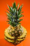 Künstlerische geschnittene, stehende Ananas auf orange Hintergrund, vertikaler Schuss Lizenzfreie Stockfotos