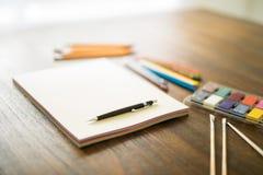 Künstlerische Werkzeuge, die auf Arbeitstabelle liegen Lizenzfreies Stockfoto