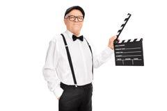 Künstlerischer älterer Mann, der ein clapperboard hält Lizenzfreie Stockfotos