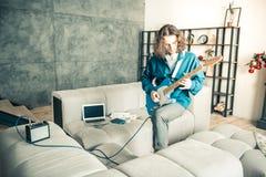 Künstlerischer junger Mann, der aktiv auf Gitarre mitten in dem Raum spielt lizenzfreies stockbild