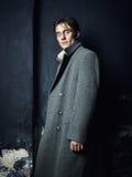 Künstlerisches dunkles Porträt des jungen schönen Mannes in einem grauen Mantel Stockbilder