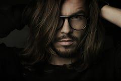 Künstlerisches dunkles Portrait des jungen schönen Mannes Stockbild