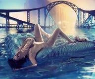 Künstlerisches Foto einer jungen Frau, die nach der Flut treibt Stockbild