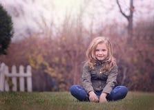 Künstlerisches Porträt im Freien eines netten blonden Mädchens, das an zu einem Zaun hält Lizenzfreie Stockfotos