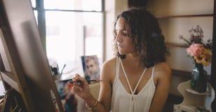 Künstlermädchen malt Bild auf Segeltuch im Studio Stockfotografie