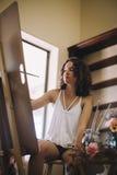 Künstlermädchen malt Bild auf Segeltuch im Studio Lizenzfreies Stockbild