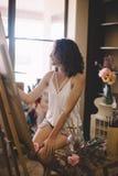 Künstlermädchen malt Bild auf Segeltuch im Studio Lizenzfreies Stockfoto