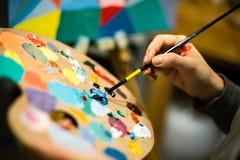 Künstlermalerei mit Acrylfarben und mischenden Tönen Lizenzfreie Stockfotografie