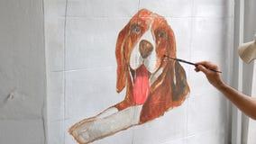 Künstlermalereispürhund auf weißer Wand stock footage