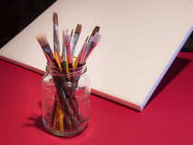 Künstlermalerpinsel im Weckglas mit Segeltuch Stockbilder