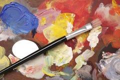 Künstlerpalette mit Lackpinselhintergrund Lizenzfreies Stockbild