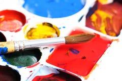 Künstlerpalette mit verschiedenen Farbfarben und -bürste Stockfotografie