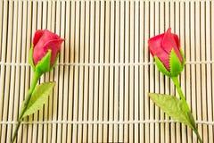 Künstlich stieg auf Bambushintergrund Stockbild