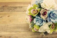 Künstliche Blumen auf hölzernem Hintergrund, Weinleseeffekt Stockfotos