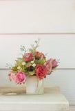 Künstliche Blumen im Korb im Weinlesethema Lizenzfreie Stockfotos