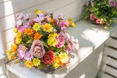 Künstliche Blumen im Korb im Weinlesethema Stockbilder