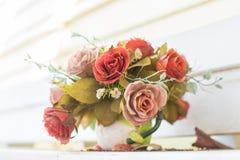 Künstliche Blumen im Korb im Weinlesethema Lizenzfreie Stockbilder