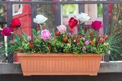 Künstliche Blumen im Korb im Weinlesethema Lizenzfreies Stockfoto