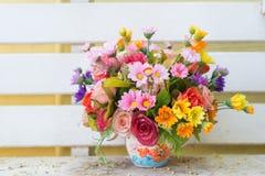 Künstliche Blumen im Korb im Weinlesethema Stockbild