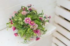Künstliche Blumen im Korb im Weinlesethema Stockfoto