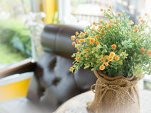 Künstliche Blumen im Vase und im Lehnsessel Lizenzfreie Stockfotos