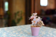 Künstliche heitre rosa Blüte im kleinen Stahltopf mit glücklichem Tagesaufkleber Lizenzfreies Stockfoto