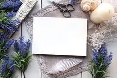 Künstliche Lavendelblumen und Modell des leeren Papiers Stockfotografie