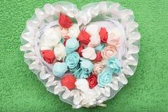 Künstliche mehrfarbige Rosen liegen in einem weißen Spitzekorb in Form eines Herzens Stockfotos
