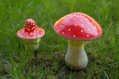 Künstliche Pilze auf einem grünen Rasen, Pilze eines Fliegenpilzes Lizenzfreie Stockfotos