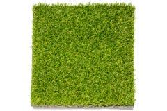 Künstliche Platte des grünen Grases auf weißem Hintergrund Stockfotografie