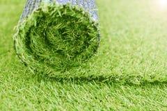 Künstliche Rasenrolle Synthetischer Grasrasen, der Hintergrund legt stockfoto