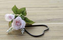 Künstliche rosa Rosen mit Metallherzen auf dem Bretterboden Lizenzfreie Stockfotos