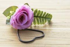 Künstliche rosa Rosen mit Metallherzen auf dem Bretterboden Stockfoto