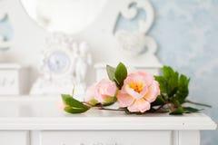Künstliche rosafarbene Blumen auf einem weißen Holztisch Stockfotos