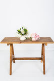 Künstliche rosafarbene Blumen auf einem weißen Holztisch Stockfotografie
