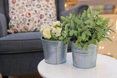 Künstliche Rosen und Grünpflanzen in den Metalltöpfen stockfoto