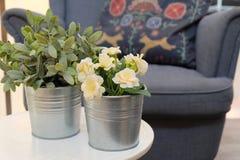 Künstliche Rosen und Grünpflanzen in den Metalltöpfen lizenzfreies stockbild