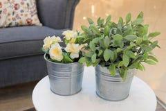 Künstliche Rosen und Grünpflanzen in den Metalltöpfen lizenzfreie stockbilder