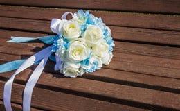 Künstlicher Blumenstrauß von weißen Rosen ist auf der Bank Lizenzfreies Stockfoto