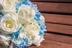 Künstlicher Blumenstrauß von weißen Rosen ist auf der Bank Lizenzfreies Stockbild